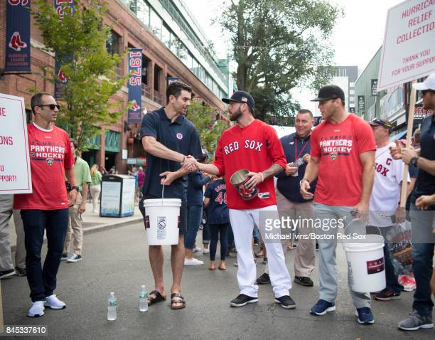 Adam McQuaid of the Boston Bruins shakes hands with Blake Swihart of the Boston Red Sox while collecting funds for hurricane relief efforts in...