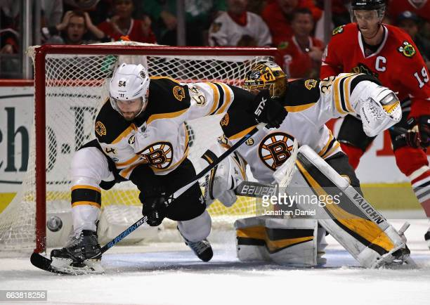 Adam McQuaid of the Boston Bruins stops a shot in front of teammate Anton Khudobin against the Chicago Blackhawks at the United Center on April 2...