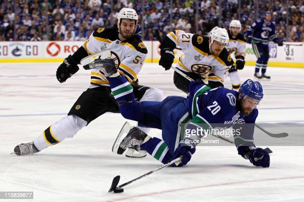 Adam McQuaid of the Boston Bruins trips Christopher Higgins of the Vancouver Canucks during Game Five of the 2011 NHL Stanley Cup Final at Rogers...