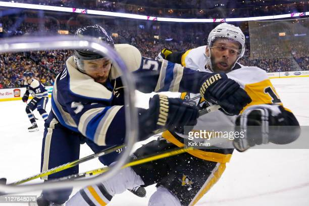 Adam McQuaid of the Columbus Blue Jackets checks Bryan Rust of the Pittsburgh Penguins into the boards during the first period on February 26 2019 at...