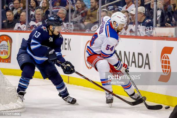 Adam McQuaid of the New York Rangers plays the puck along the boards as Brandon Tanev of the Winnipeg Jets gives chase during first period action at...