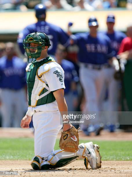 Adam Melhuse of the Oakland Athletics looks on after Carlos Lee of the Texas Rangers celebrates after hitting a solo home run on August 9, 2006 at...