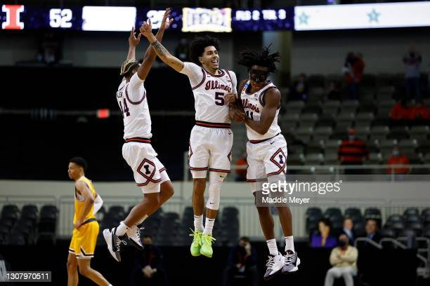 Adam Miller, Andre Curbelo, and Ayo Dosunmu of the Illinois Fighting Illini celebrate against the Drexel Dragons in the second half of the first...