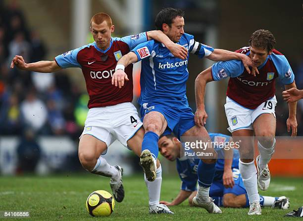 Adam Miller of Gillingham battles for the ball with Steve Sidwell and Stiliyan Petrov of Aston Villa during the FA Cup sponsored by Eon third round...
