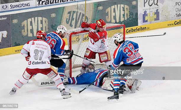 Adam Mitchell and Aris Brimanis of Hannover Andre Savage Patrick Ehelechner and Alain Nasreddine of Nuremberg battle for the puck during the fourth...