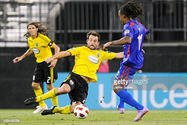 Adam Moffat of the Columbus Crew dives in to kick the ball away from Guillermo Ramirez of Guatemala Municipal on August 18 2010 at Crew Stadium in...