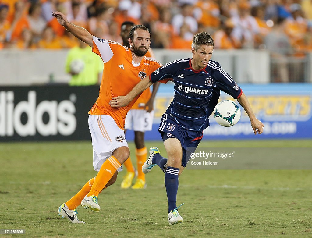 Adam Moffat #16 of the Houston Dynamo battles forthe ball against Logan Pause #12 of the Chicago Fire at BBVA Compass Stadium on July 27, 2013 in Houston, Texas.