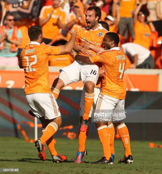 Adam Moffat of the Houston Dynamo celebrates his goal in the nineteenth minute with teammate Jermaine Taylor and Will Bruin during the first half of...