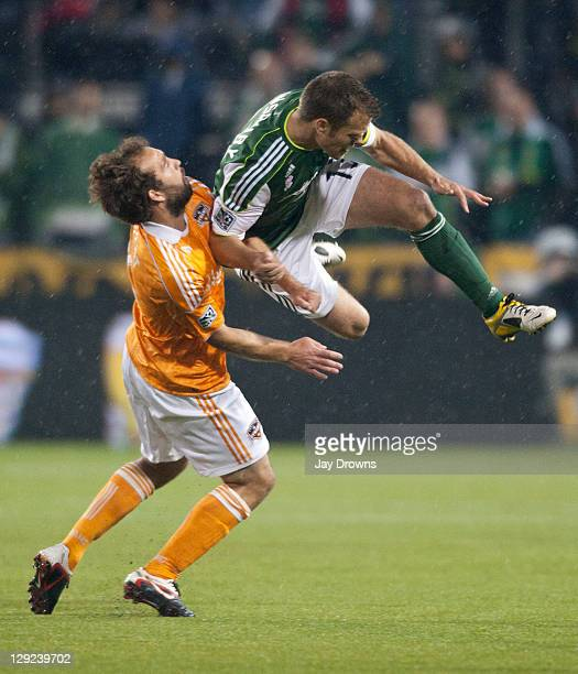 Adam Moffat of the Houston Dynamo collides with Jack Jewsbury of the Portland Timbers during the first half at JeldWen Field on October 14 2011 in...