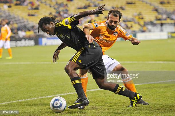 Adam Moffat of the Houston Dynamo holds back Andres Mendoza of the Columbus Crew in the second half on September 14 2011 at Crew Stadium in Columbus...