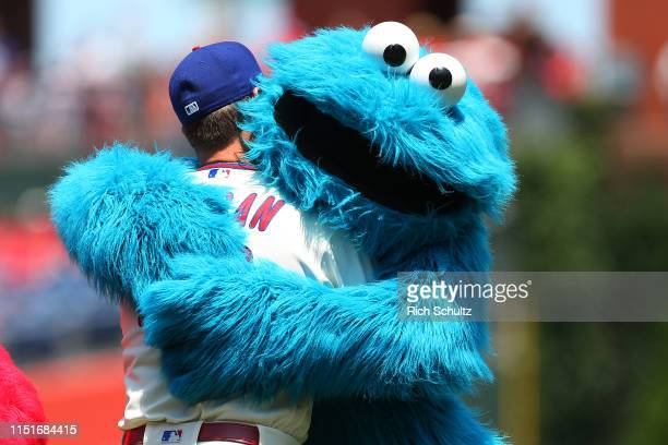 Adam Morgan of the Philadelphia Phillies gets a hug from the Cookie Monster before a game against the Miami Marlins at Citizens Bank Park on June 23,...