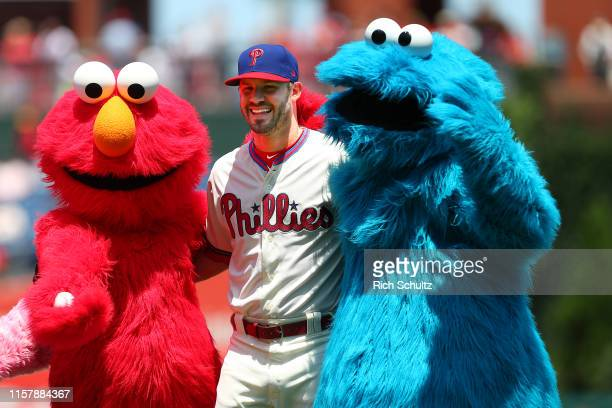 Adam Morgan of the Philadelphia Phillies poses with Elmo and the Cookie Monster from Sesame Street before a game against the Miami Marlins at...