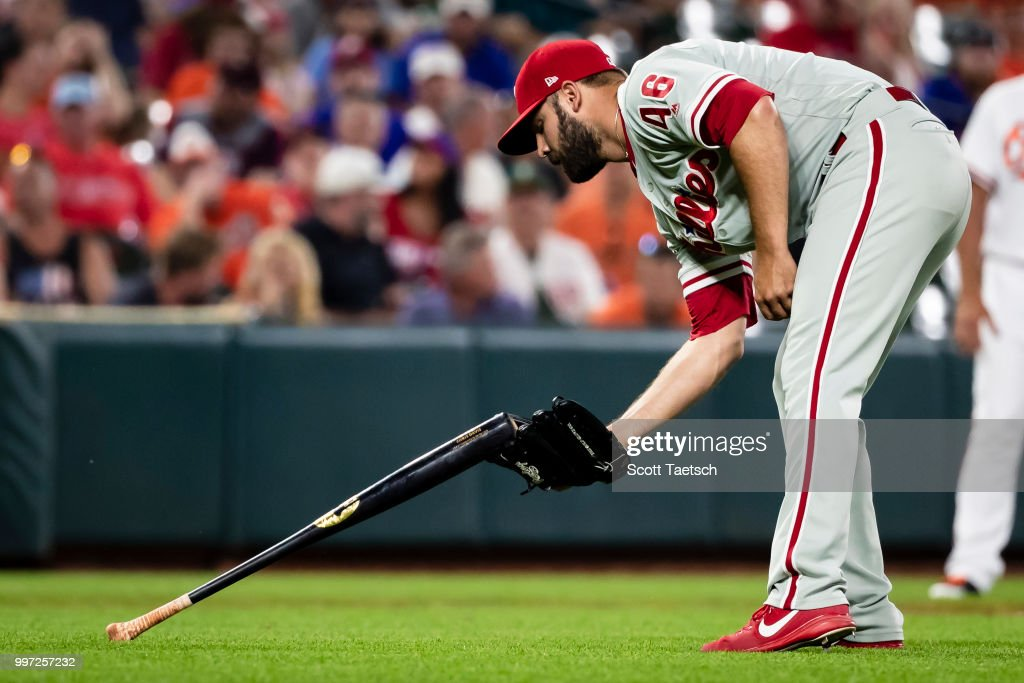 Adam Morgan #46 of the Philadelphia Phillies retrieves the bat of Chris Davis #19 of the Baltimore Orioles (not pictured) during the eighth inning at Oriole Park at Camden Yards on July 12, 2018 in Baltimore, Maryland.