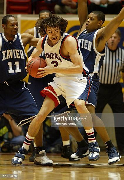 Adam Morrison of the Gonzaga Bulldogs looks to move the ball as he is triple teamed by the Xavier Musketeers during the First Round of the 2006 NCAA...
