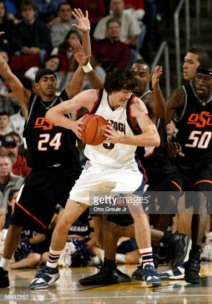 Adam Morrison of the Gonzaga Bulldogs posts up against Jameson Curry, Aaron Pettway and an unidentified player of the Oklahoma State Cowboys at Key...