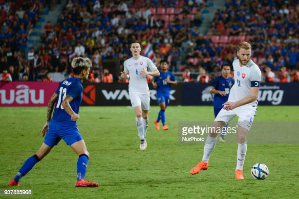 Adam Nemec of Slovakia and Thailand's Philip Roller for the ball during their King Cup 46th soccer final match at Rajamangala national stadium in...