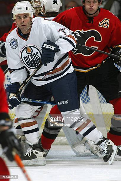 Adam Oates of the Edmonton Oilers screens the goaltender in front of the Flames net as Robyn Regehr of the Calgary Flames defends during the game at...
