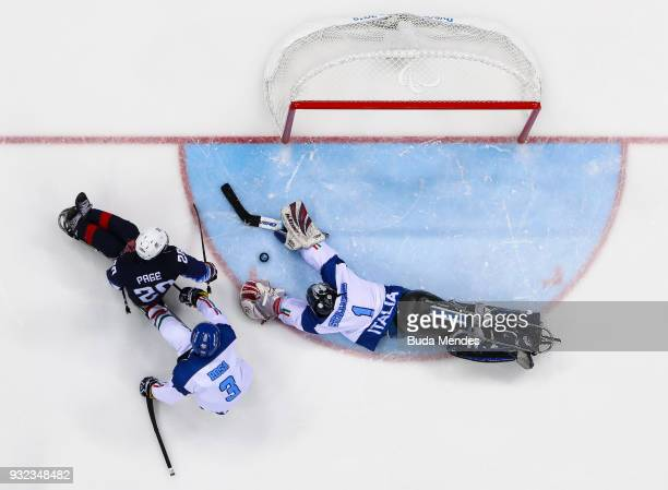 Adam Page of the United States battles for the puck with a goalkeeper Santino Stillitano of Italy in the Ice Hockey semifinals game between United...