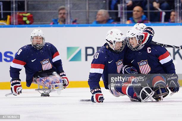 Adam Page of the United States celebrates with team mate Andy Yohe after scoring his team's first goal during the Ice Sledge Hockey Preliminary Round...