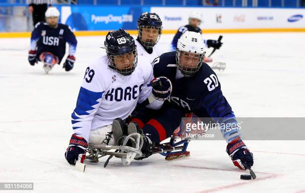 Adam Page of United States battles for the puck with Hoon Ji Lee of Korea in the Ice Hockey Preliminary Round Group B game between United States and...