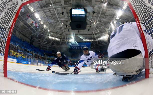 Adam Page of United States scores the opening goal over Gyun Man Yu goaltender of Korea in the Ice Hockey Preliminary Round Group B game between...