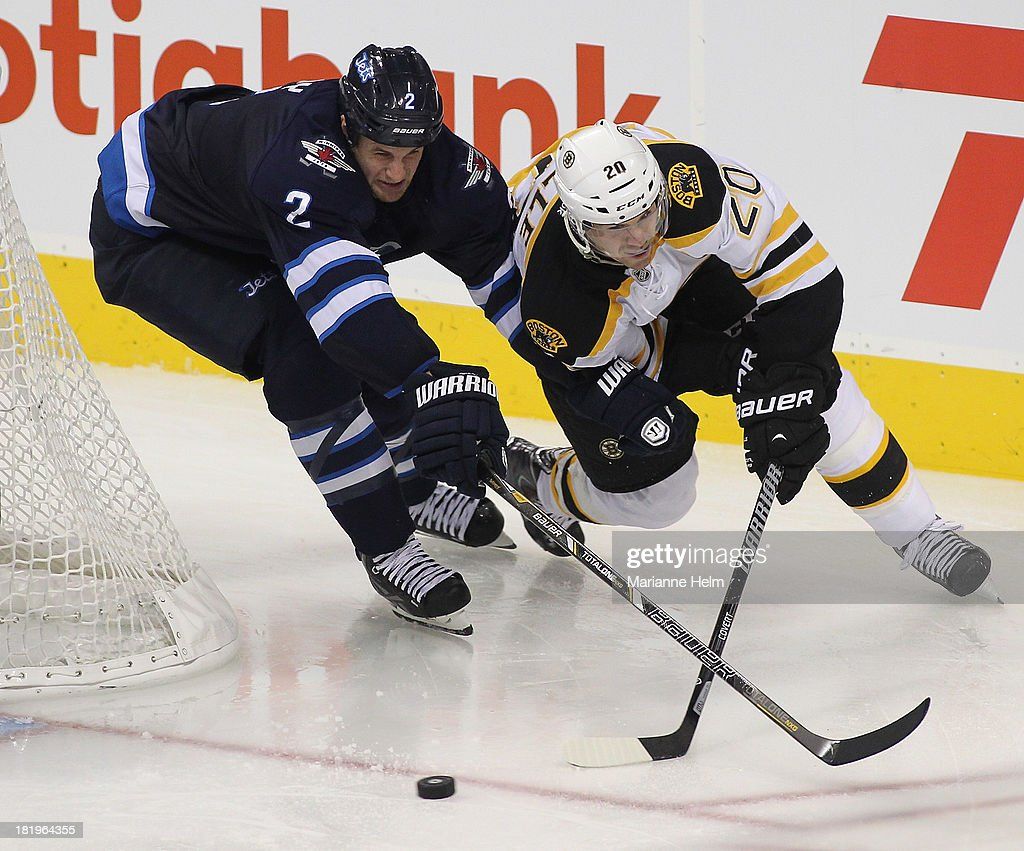 Adam Pardy #2 of the Winnipeg Jets battles for the puck with Daniel Paille #20 of the Boston Bruins in third period action during an NHL preseason game at the MTS Centre on September 26, 2013 in Winnipeg, Manitoba, Canada.