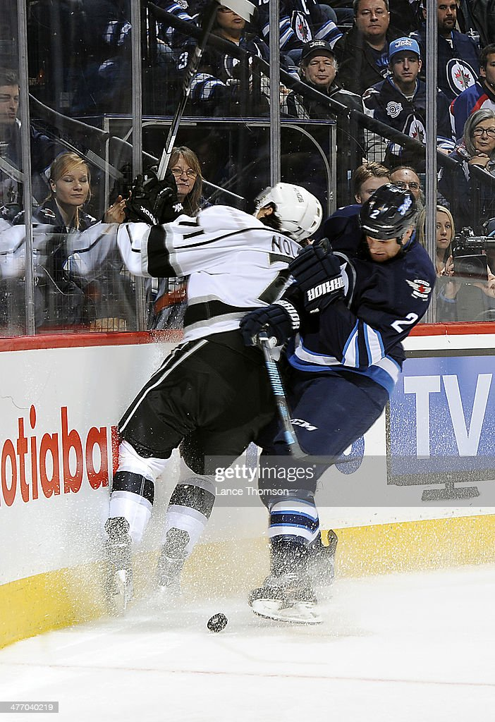 Adam Pardy #2 of the Winnipeg Jets checks Jordan Nolan #71 of the Los Angeles Kings into the end boards as the puck squirts loose during third period action at the MTS Centre on March 6, 2014 in Winnipeg, Manitoba, Canada.
