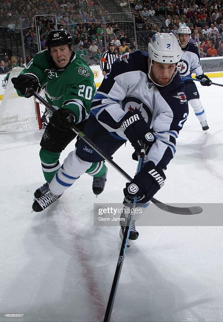 Adam Pardy #2 of the Winnipeg Jets tries to keep the puck away against Cody Eakin #20 of the Dallas Stars at the American Airlines Center on March 24, 2014 in Dallas, Texas.
