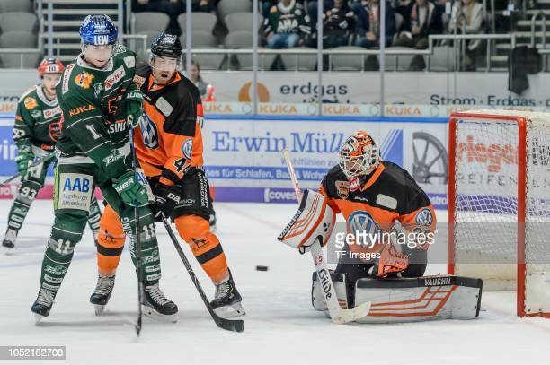 Adam Payerl of Augsburger Panther Bjoern Krupp of Grizzlys Wolfsburg and Goalkeeper Gerald Kuhn of Grizzlys Wolfsburg battle for the ball during the...