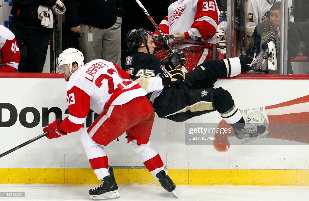 Adam Payerl #45 of the Pittsburgh Penguins is checked by Brian Lashoff #23 of the Detroit Red Wings during the game at Consol Energy Center on April 9, 2014 in Pittsburgh, Pennsylvania.