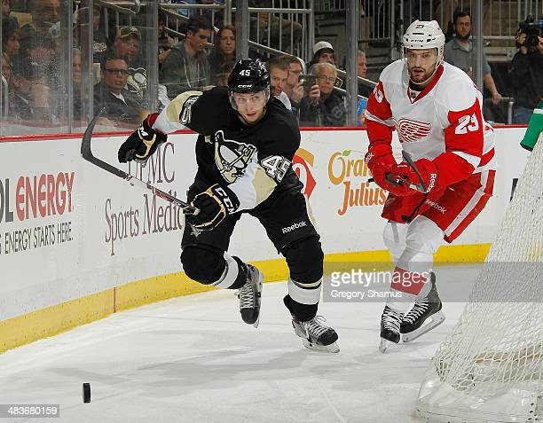 Adam Payerl of the Pittsburgh Penguins skates for the loose puck alongside Brian Lashoff of the Detroit Red Wings on April 9 2014 at Consol Energy...