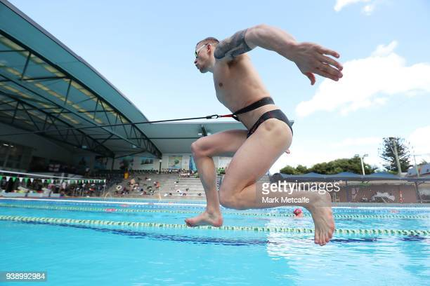 Adam Peaty jumps into the pool during a Team England media opportunity ahead of the 2018 Gold Coast Commonwealth Games at Somerville High School on...