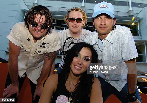 Adam Pedretti Jesse Hooper Ella Hooper and Warren Jenkins of the Australian band Killing Heidi poses for photographers with a cake and candle to...