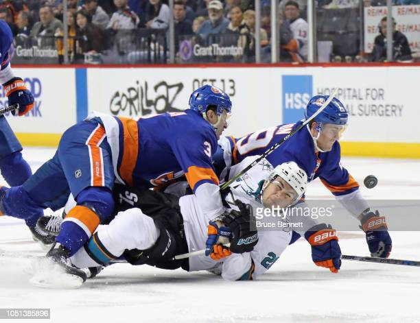 Adam Pelech and Brock Nelson of the New York Islanders combine to hit Timo Meier of the San Jose Sharks during the first period at the Barclays...