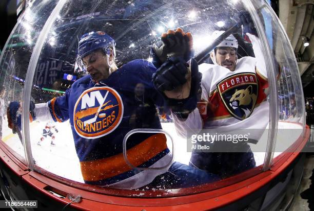 Adam Pelech of the New York Islanders and Brian Boyle of the Florida Panthers crash the boards during their game at Barclays Center on November 09...