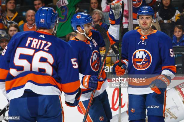 Adam Pelech of the New York Islanders celebrates his first period goal with teamates Andrew Ladd and Tanner Fritz against the Pittsburgh Penguins at...