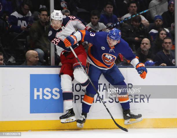 Adam Pelech of the New York Islanders checks Oliver Bjorkstrand of the Columbus Blue Jackets during the first period at the NYCB Live's Nassau...