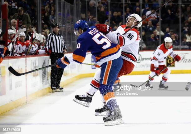 Adam Pelech of the New York Islanders checks Teuvo Teravainen of the Carolina Hurricanes during the first period at the Barclays Center on March 18...