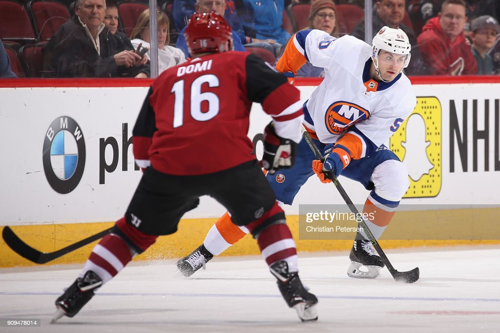 Adam Pelech #50 of the New York Islanders controls the puck ahead of Max Domi #16 of the Arizona Coyotes during the NHL game at Gila River Arena on January 22, 2018 in Glendale, Arizona. The Coyotes defeated the Islanders 3-2 in overtime.