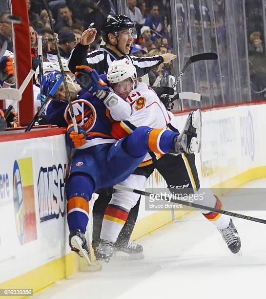 Adam Pelech of the New York Islanders is checked into the boards by Micheal Ferland of the Calgary Flames during the second period at the Barclays...