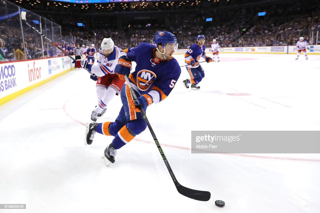 Adam Pelech #50 of the New York Islanders skates with the puck against Rick Nash #61 of the New York Rangers in the third period during their game at Barclays Center on February 15, 2018 in the Brooklyn borough of New York City.