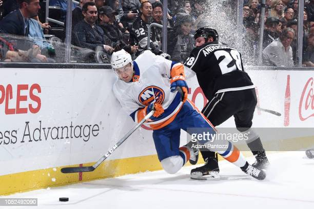 Adam Pelech of the New York Islanders tries to clear the puck as he is checked by Jaret AndersonDolan of the Los Angeles Kings during the first...