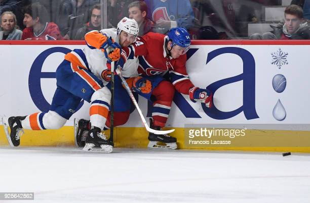 Adam Pelech of the New York Islanders tries to slow down Charles Hudon of the Montreal Canadiens in the NHL game at the Bell Centre on February 28...