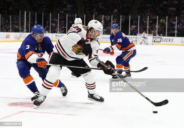 Adam Pelech of the New York Islanders trips Brandon Saad of the Chicago Blackhawks during their game at Nassau Veterans Memorial Coliseum on January...