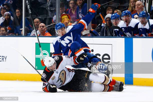 Adam Pelech of the New York Islanders trips over Derek Grant of the Anaheim Ducks at Nassau Veterans Memorial Coliseum on January 20 2019 in...