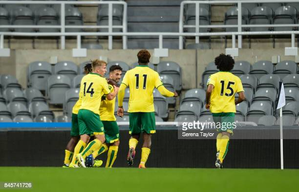 Adam Phillips of Norwich City celebrates with teammates after he scores the equalising goal from the penalty spot during the Premier League 2 match...