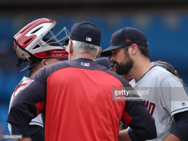 Adam Plutko of the Cleveland Indians is visited on the mound by pitching coach Carl Willis in the second inning during MLB game action against the...