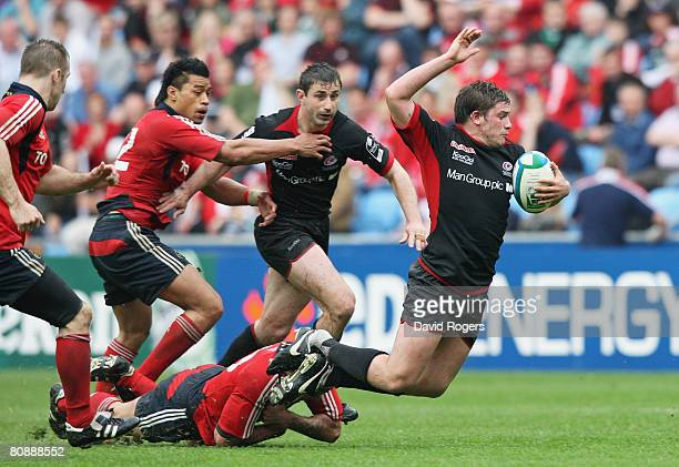 Adam Powell of Saracens is brought down by the tackle from Rua Tipoki of Munster during the Heineken Cup Semi Final match between Saracens and...