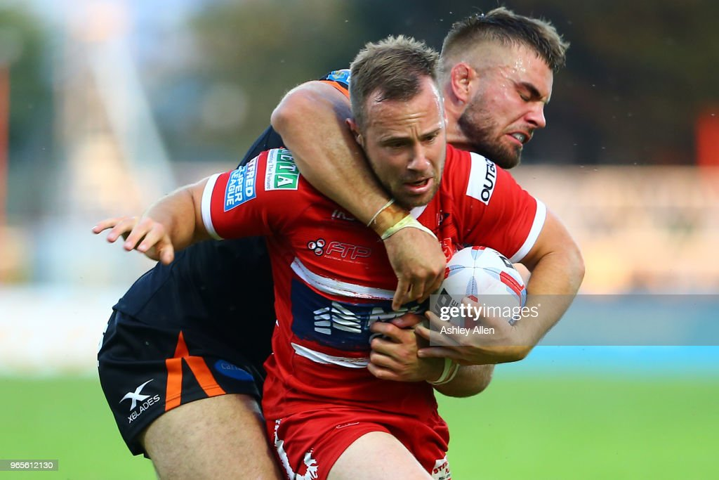 Adam Quinlan of Hull KR is slowed down by Mike McMeeken of Castleford Tigers during the Roger Millward Trophy match between Hull KR and Castleford Tigers as part of the Betfred Super League at KCOM Stadium on June 1, 2018 in Hull, England.