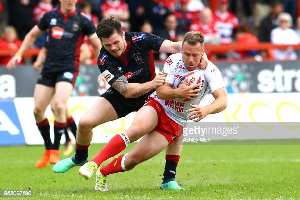 Adam Quinlan of Hull KR is tackled by John Bateman of Wigan Warriors during round six of the Ladbrokes Challenge Cup at KCOM Craven Park on May 13...